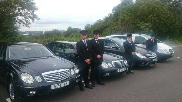 members of staff with funeral cars